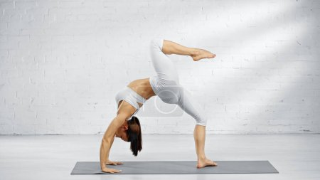 Photo for Side view of barefoot woman in upward bow pose on yoga mat at home - Royalty Free Image