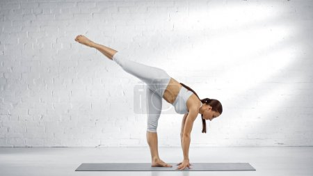Young woman standing in one legged downward facing dog yoga pose