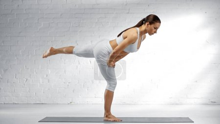 Photo pour Vue latérale de la femme en tenue de sport blanche debout dans la posture de yoga guerrier - image libre de droit