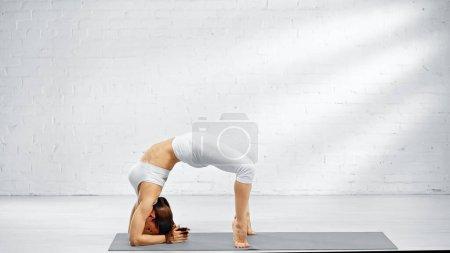 Foto de Vista lateral de la mujer de pie en postura de yoga en la estera - Imagen libre de derechos