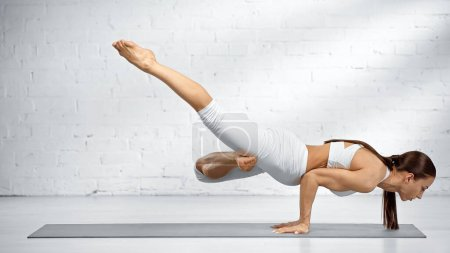 Photo for Side view of woman balancing on hands while practicing yoga near white wall - Royalty Free Image
