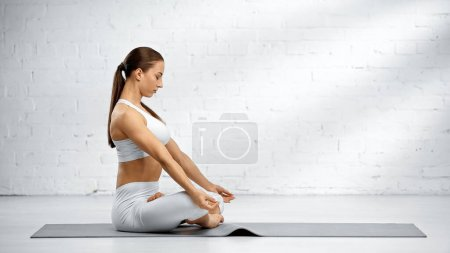 Photo for Side view of woman meditating in yoga pose - Royalty Free Image