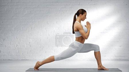 Photo pour Vue latérale de la femme en tenue de sport blanche méditant à la maison - image libre de droit