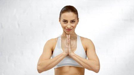 Photo pour Sportive souriante montrant les mains payantes à la maison - image libre de droit