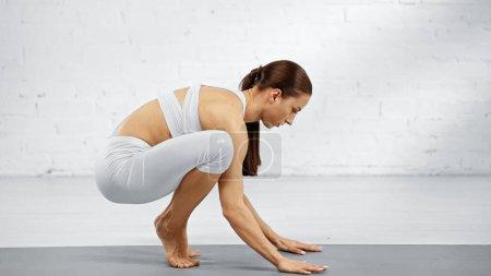Photo pour Vue latérale de la femme en tenue de sport équilibrage sur tapis de yoga - image libre de droit
