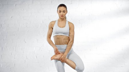 Foto de Mujer joven en top deportivo practicando yoga cerca de la pared blanca - Imagen libre de derechos