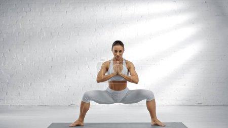 Photo pour Fit femme debout dans la pose de yoga avec les mains priantes sur le tapis - image libre de droit