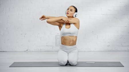 Sportswoman stretching arm and listening music in headphones near smartphone