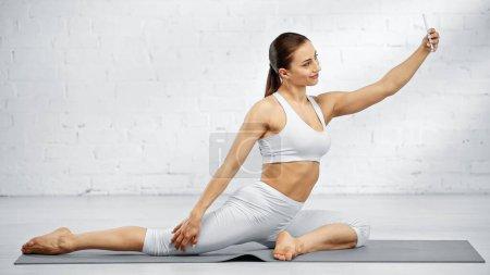 Deportista sonriente tomando selfie en el celular en la esterilla de yoga