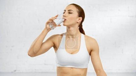 Sportswoman drinking water near white wall