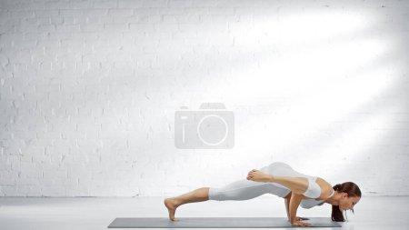 Jeune femme pratiquant le yoga près du mur blanc à la maison