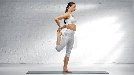 Photo pour Jolie femme étirant la jambe tout en se tenant debout sur le tapis de yoga à la maison - image libre de droit
