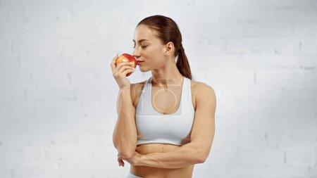 Sportswoman smelling fresh apple at home