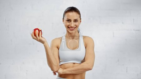 Positive sportswoman holding apple and looking at camera