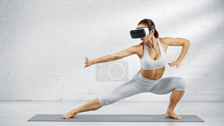 Barefoot woman in vr headset standing on yoga mat