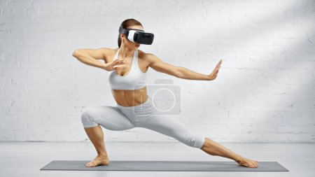 Photo for Fit woman using virtual reality headset on yoga mat - Royalty Free Image
