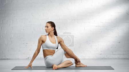 Photo for Sportswoman sitting in half lord of fishes pose - Royalty Free Image
