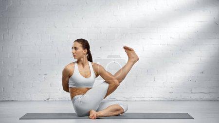 Junge Frau macht Yoga auf Matte zu Hause