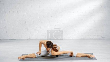 Brunette sportswoman stretching while sitting in split