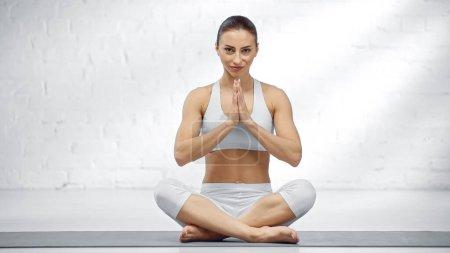 Photo pour Femme assise dans une pose de yoga facile et montrant les mains priantes - image libre de droit