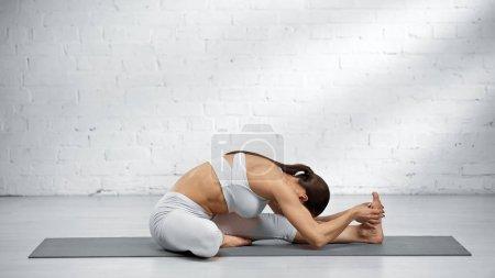 Photo pour Sportswoman faisant une pose de yoga avant jambe à la maison - image libre de droit