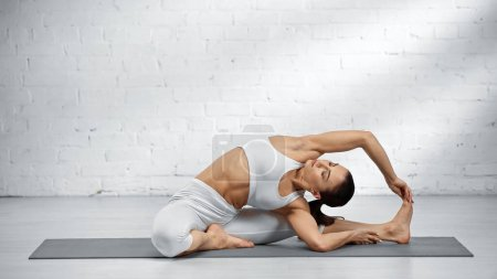 Barefoot woman in white sports top practicing yoga position