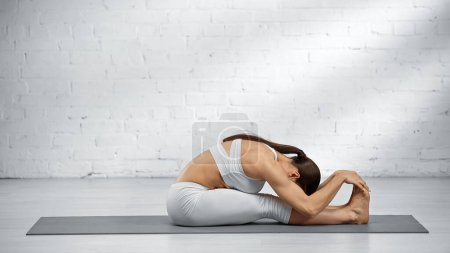 Photo for Woman doing seated forward fold yoga pose at home - Royalty Free Image