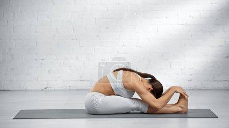 Woman doing seated forward fold yoga pose at home