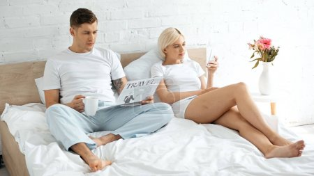 Photo for Tattooed man reading travel newspaper and holding cup of coffee near woman using smartphone in bed - Royalty Free Image