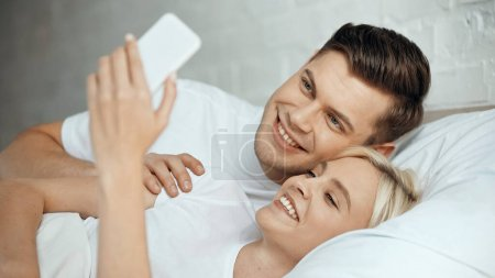 szczęśliwy młody mężczyzna i kobieta biorąc selfie na smartfon w sypialni