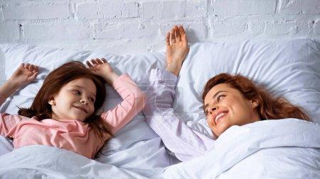 Photo pour Mère et enfant positifs se regardant sur le lit - image libre de droit