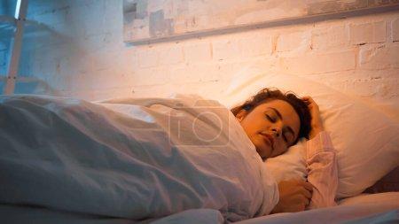 Kobieta śpiąca w nocy na łóżku
