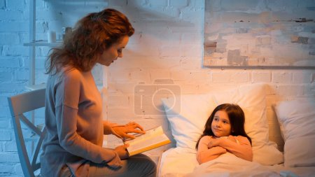 Parent reading book near child on bed
