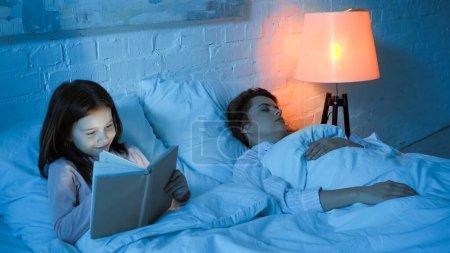 Photo pour Souriant fille lecture livre tandis que mère dormir sur le lit - image libre de droit