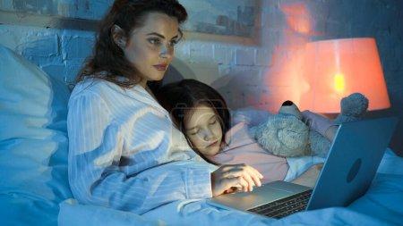 Woman using laptop near sleeping kid on bed