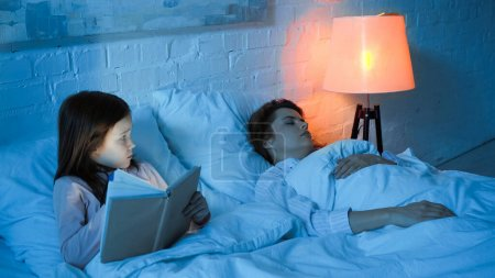 Photo for Girl with book looking at sleeping mother on bed during night - Royalty Free Image