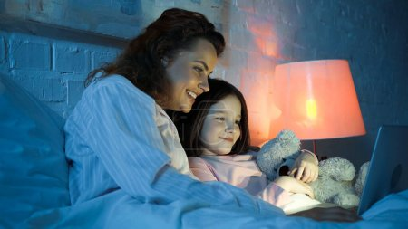 Photo for Smiling woman using laptop near daughter with soft toy on bed - Royalty Free Image