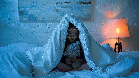 Photo pour Enfant tenant jouet tout en étant assis sous la couverture sur le lit - image libre de droit