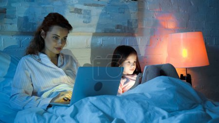 Photo for Woman using laptop near daughter with digital tablet on bed in night - Royalty Free Image