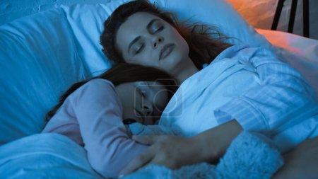 Photo pour Femme étreignant l'enfant tout en dormant pendant la nuit - image libre de droit
