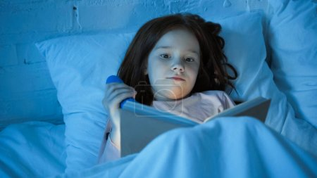 Child holding flashlight and reading book on blurred foreground on bed