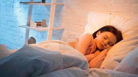 Preadolescent kid sleeping on white bedding in evening