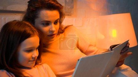 Photo pour Mère et fille préadolescente lecture livre flou dans la chambre - image libre de droit