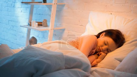 Photo for Preteen child sleeping on bed in evening - Royalty Free Image