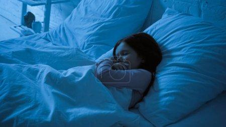 Preteen kid hugging blanket while sleeping on bed