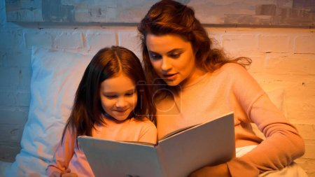 Photo for Smiling kid reading book with mom on bed - Royalty Free Image