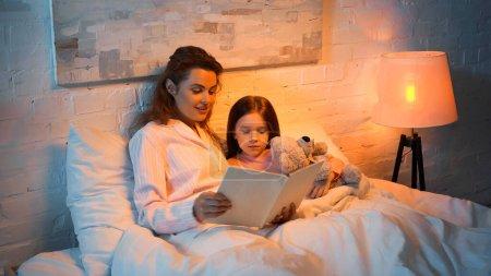 Photo pour Mère souriante en pyjama livre de lecture près de l'enfant avec jouet doux sur le lit - image libre de droit