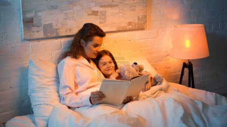 Photo for Happy girl with teddy bear lying near mother reading book on bed - Royalty Free Image