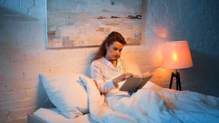 Photo pour Femme en pyjama livre de lecture près du lampadaire dans la chambre - image libre de droit