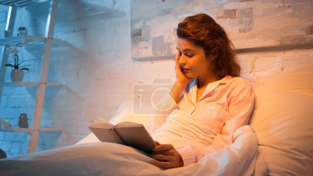 Exhausted woman with book sitting on bed in evening